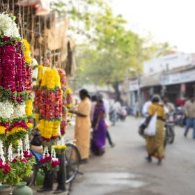 A flower necklace being sold at a traditional market in India.